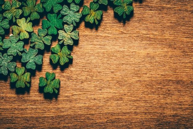 Trevos de madeira verde de quatro folhas na placa de madeira Foto Premium