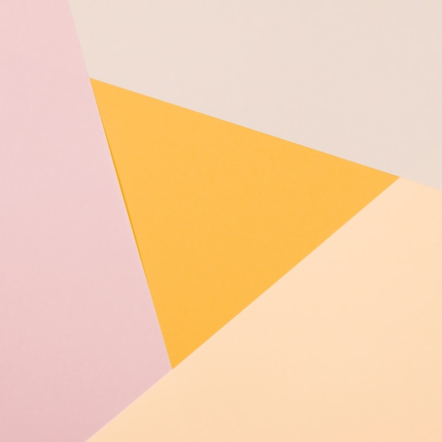 Triângulo amarelo com papel colorido plano geométrico fundo Foto gratuita