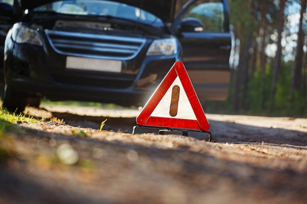 Triângulo de advertência atrás de um carro quebrado. Foto Premium
