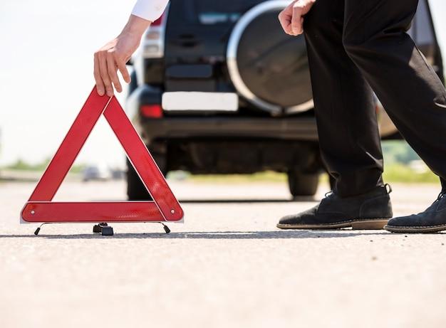 Triângulo de advertência vermelho com um carro dividido na estrada. Foto Premium