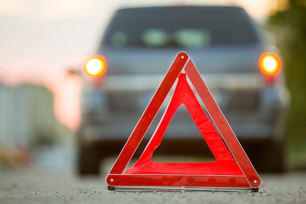 Triângulo de emergência vermelho parar sinal e carro quebrado em uma rua da cidade. Foto Premium