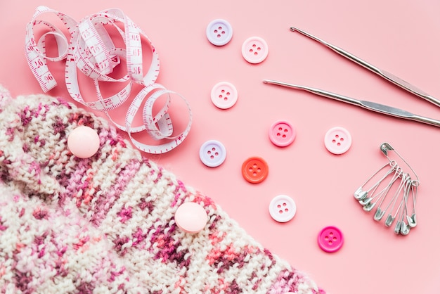 Tricô de crochê; fita métrica; botões; alfinetes de segurança e agulhas no pano de fundo rosa Foto gratuita