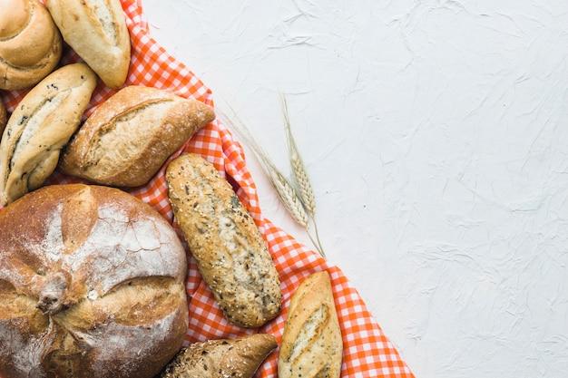 Trigo perto de pão e tecido Foto gratuita