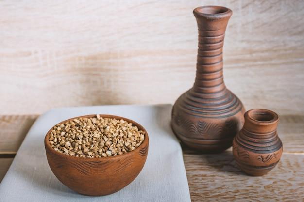Trigo seco na tigela de barro marrom na mesa de madeira. grãos sem glúten para uma dieta saudável Foto Premium