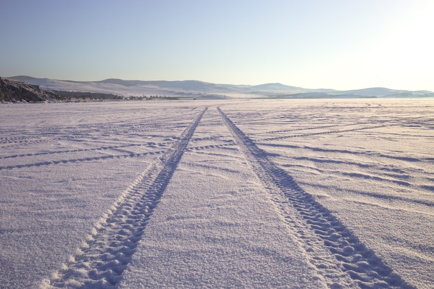 Trilhos de roda na estrada de inverno coberta de neve Foto Premium