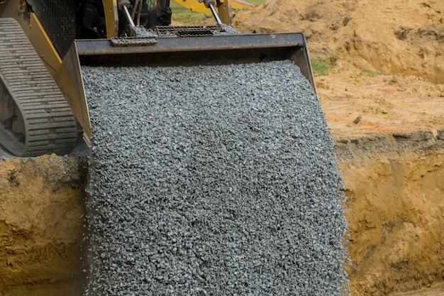 Trincheira de aterro para caçamba de escavadeira para aterro de pedra da fundação Foto Premium
