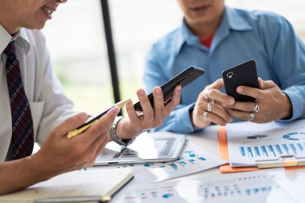 Tripulação de asiáticos dois gerentes de negócios de meia-idade trabalhando com novo projeto de inicialização enquanto está sentado. Foto Premium