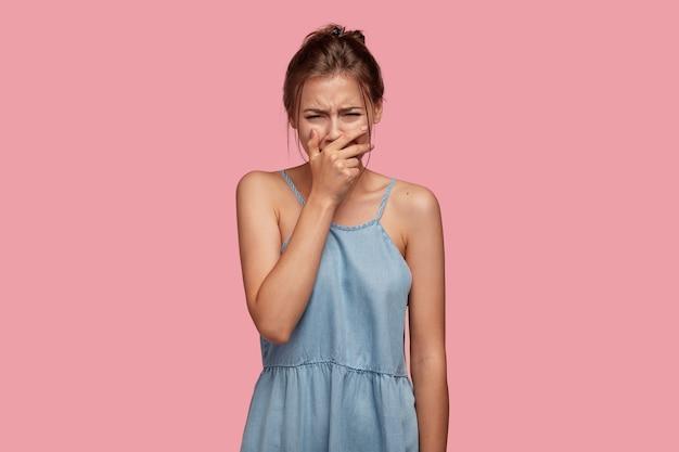 Triste deprimida e decepcionada jovem chora em desespero por ter perdido algo valioso, expressa emoções negativas, cobre a boca, sendo infeliz e deprimida, lamenta por ter dito palavrões a uma pessoa próxima Foto gratuita