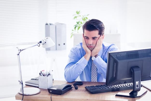 Triste empresário sentado em sua mesa Foto Premium