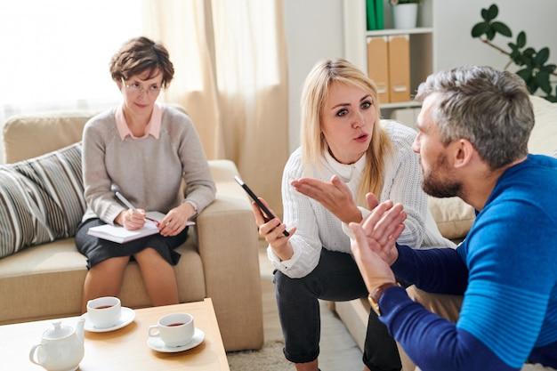 Triste esposa brigando com o marido traindo na sessão de terapia Foto Premium