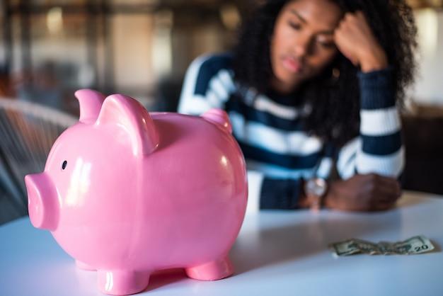 Triste frustrada mulher negra com mealheiro Foto Premium