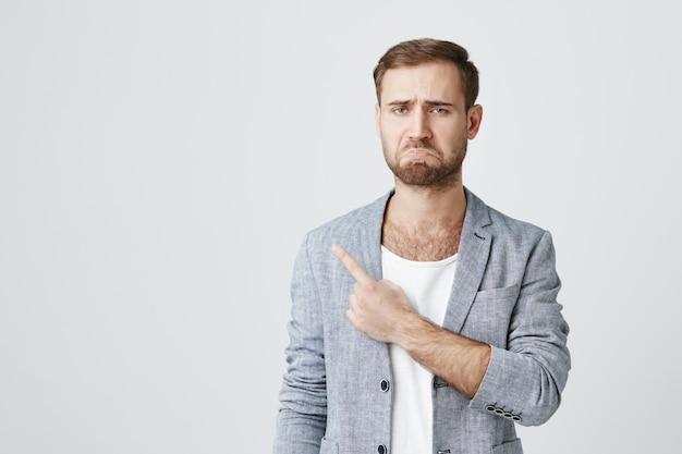 Triste homem barbudo triste fazendo beicinho, apontando para o canto esquerdo Foto gratuita
