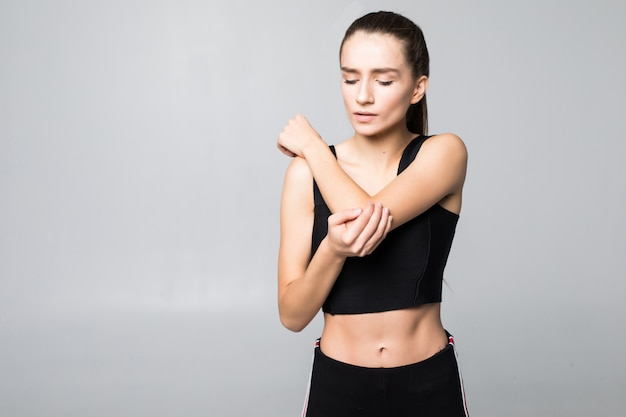 Triste jovem morena ferida no braço durante o treinamento esportivo, toca o pulso isolado na parede branca Foto gratuita