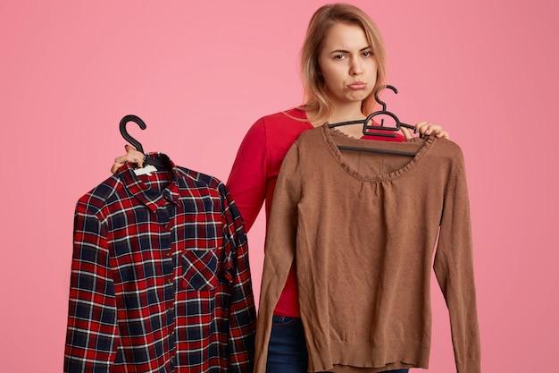 Triste mulher caucasiana insatisfeita bolsas lábios, detém duas camisas oh cabides no shopping, descontentamento com o preço alto, isolado sobre rosa Foto Premium