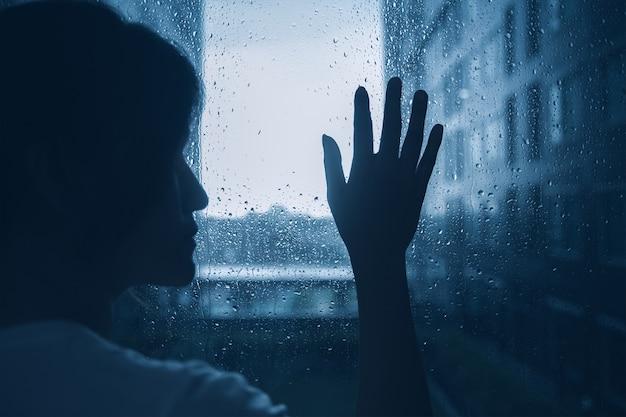 Triste sozinho menina mulher adolescente olhando para fora janelas chovendo gotas escuro humor escuro luz Foto Premium