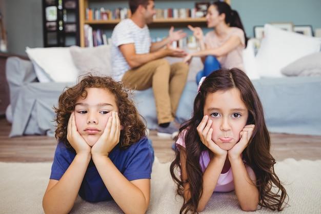 Tristes irmãos deitado no tapete enquanto os pais sentados Foto Premium