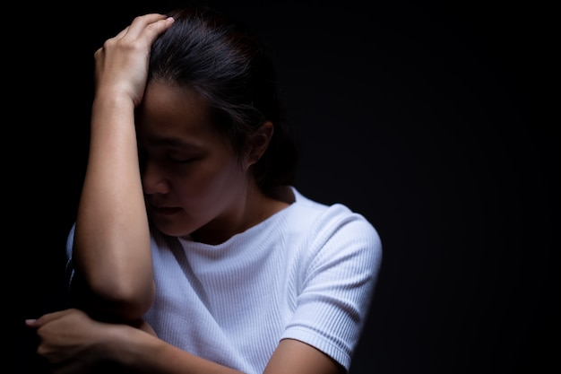 Tristeza de uma mulher no escuro Foto Premium
