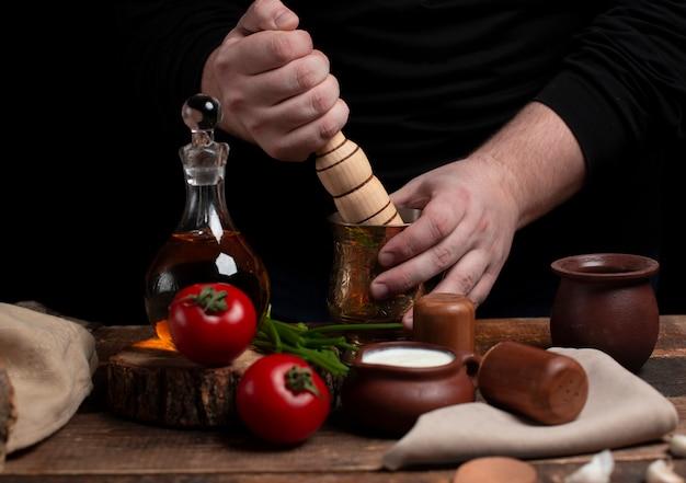 Triturar especiarias com rolo de madeira em cima da mesa com legumes Foto gratuita
