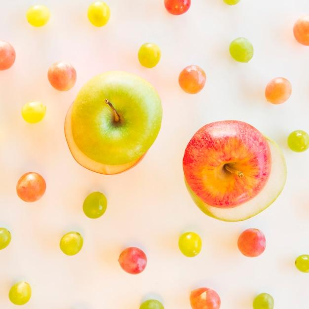 Trocar fatias de maçã verde e vermelho rodeado de uvas no pano de fundo branco Foto gratuita