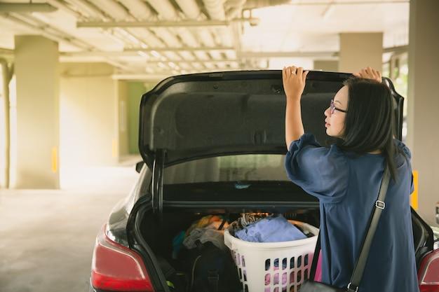 Tronco de carro aberto de mulher no estacionamento Foto Premium