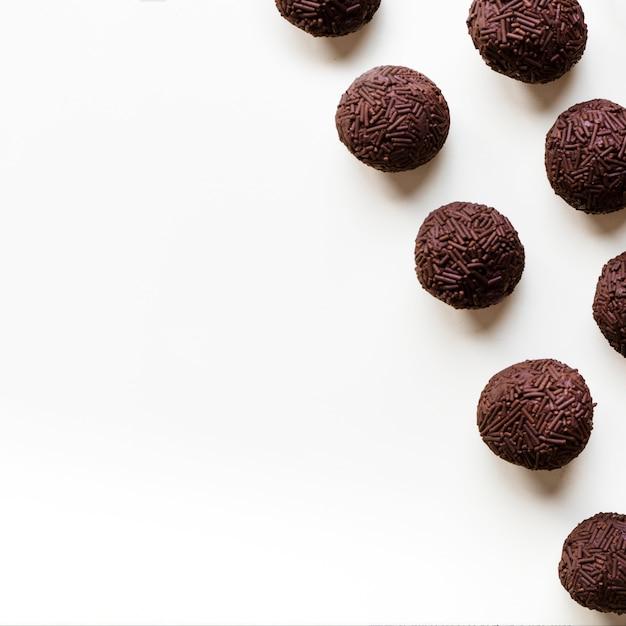 Trufas de chocolate em uma fileira no fundo branco Foto Premium