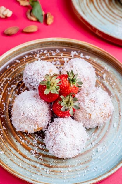 Trufas de morango cobertas com pedaços de coco Foto gratuita