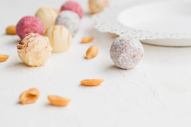 Trufas envidraçadas coloridas espalhadas na mesa branca Foto gratuita
