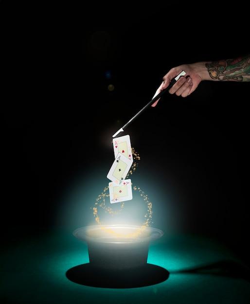 Truque mágico do cartão de jogo do desempenho sobre o chapéu alto com luzes de incandescência de encontro ao fundo preto Foto gratuita