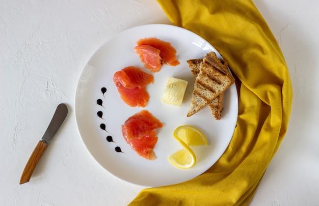 Truta, manteiga e pão em um prato. fundo branco Foto Premium