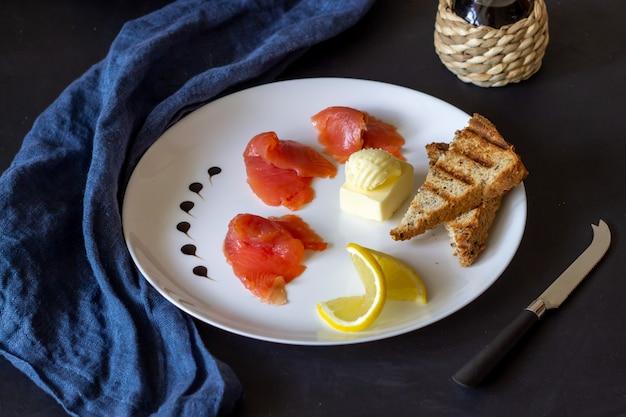 Truta, manteiga e pão em um prato. fundo escuro Foto Premium