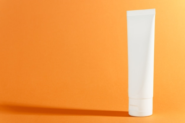 Tubo de creme em laranja ensolarado brilhante com sombra Foto Premium