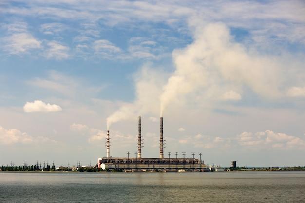 Tubos altos da central térmica com fumaça espessa refletida na superfície da água lke. poluição do meio ambiente. Foto Premium