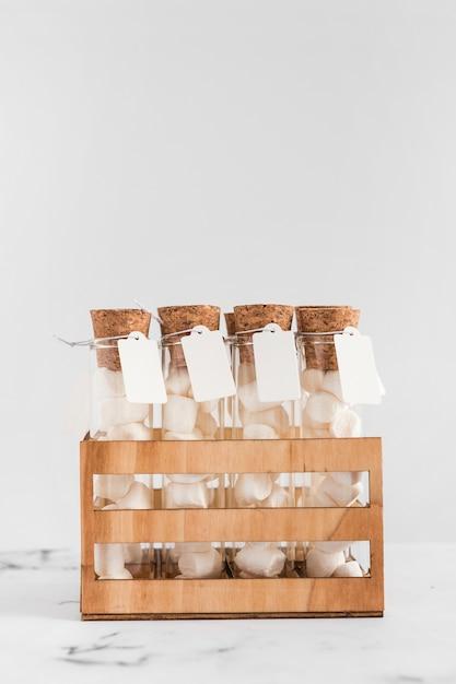 Tubos de ensaio de marshmallow com tag em caixa contra fundo branco Foto gratuita