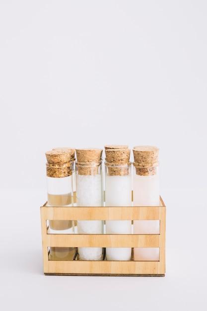Tubos de ensaio de produto orgânico spa dispostos em recipiente de madeira na superfície branca Foto gratuita