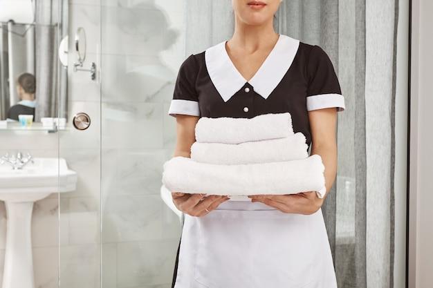 Tudo é fresco e limpo. retrato recortado de faxineiro em uniforme de empregada segurando o pacote de toalhas brancas. funcionário trouxe tudo que o cliente encomendou para o seu quarto de hotel Foto gratuita