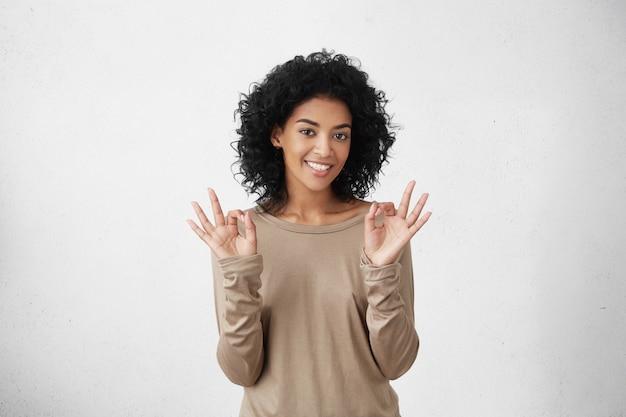 Tudo é perfeito. mulher feliz estudante de pele escura positiva mostrando gesto bem com ambas as mãos, tendo bom humor depois de passar com êxito em todos os exames na faculdade. Foto gratuita