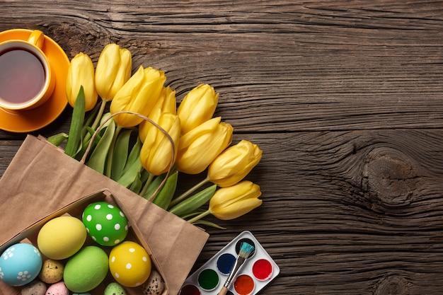 Tulipas amarelas, um ninho com ovos de páscoa, cores brilhantes e uma paleta em um fundo de madeira. vista superior com espaço de cópia. Foto Premium