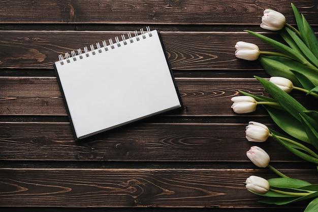 Tulipas brancas em uma mesa de madeira com um caderno vazio. composição plana, vista superior Foto Premium