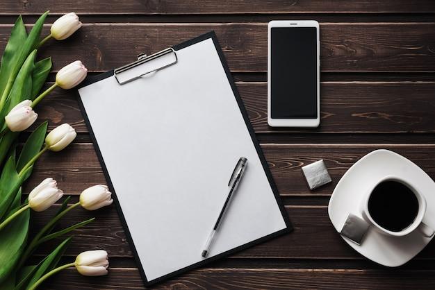 Tulipas brancas em uma mesa de madeira com um tablet de papel vazio e smartphone e uma xícara de café Foto Premium