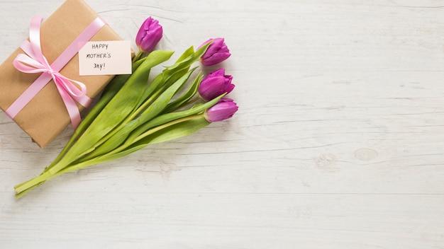 Tulipas com presente e feliz dia das mães inscrição Foto gratuita