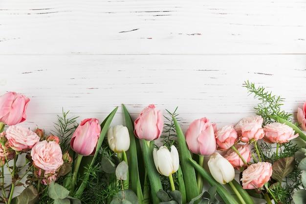 Tulipas cor de rosa e rosas em fundo de prancha de madeira Foto gratuita
