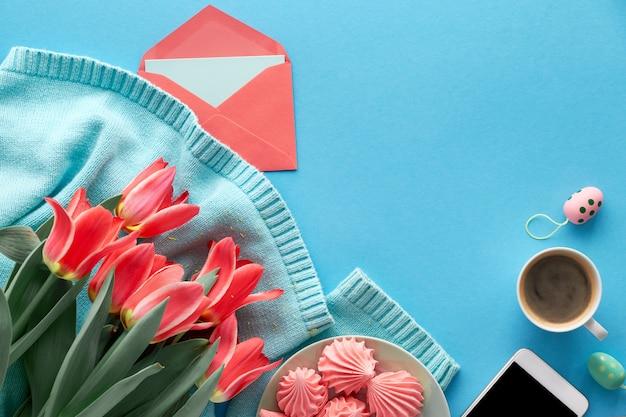 Tulipas cor de rosa na camisola de algodão, cartões e envelopes, telefone celular e café Foto Premium