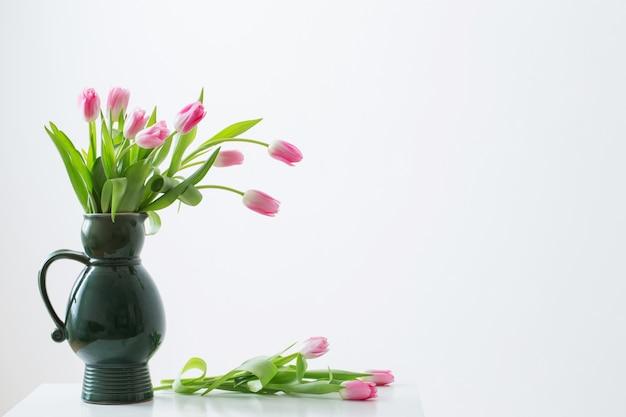 Tulipas cor de rosa no jarro verde sobre fundo branco Foto Premium