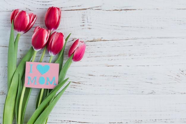 Tulipas e cartão para o dia de mãe no fundo de madeira Foto gratuita
