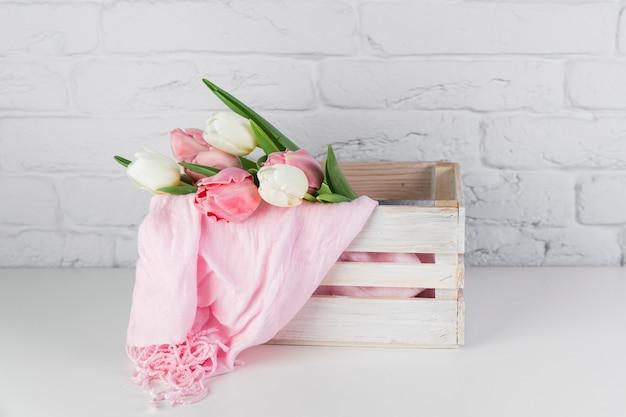 Tulipas e lenço rosa dentro da caixa de madeira na mesa contra a parede de tijolos brancos Foto gratuita