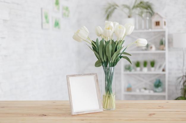 Tulipas em um vaso sobre uma mesa de madeira. interior escandinavo. brincar. Foto Premium