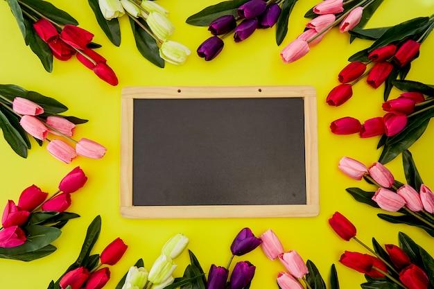 Tulipas na mesa de madeira com placa de giz preto vazio Foto Premium
