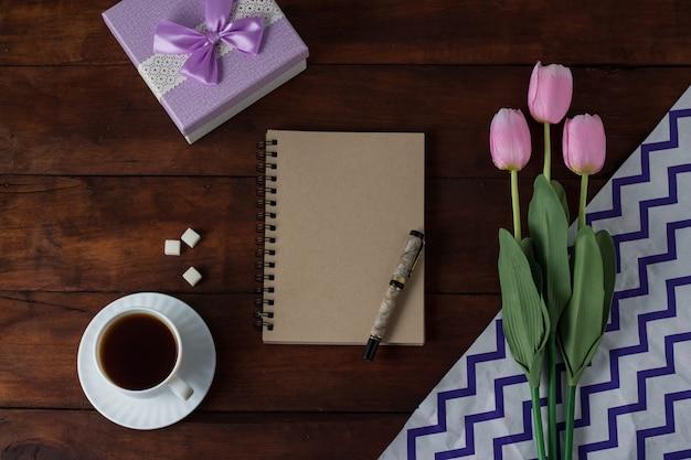 Tulipas, presente, xícara com café, caderno sobre uma superfície de madeira escura. vista plana e superior Foto Premium
