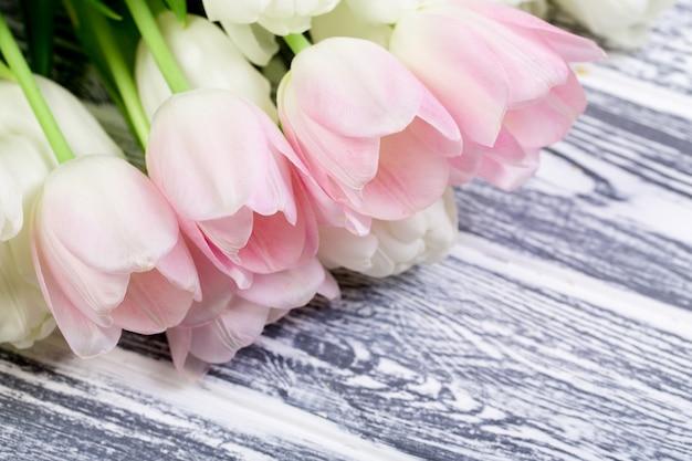 Tulipas rosa muito brancas e brancas em branco, cinza de madeira backgrou Foto Premium