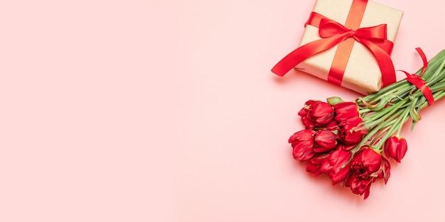 Tulipas vermelhas com caixa de presente em um fundo vermelho para dia dos namorados Foto Premium